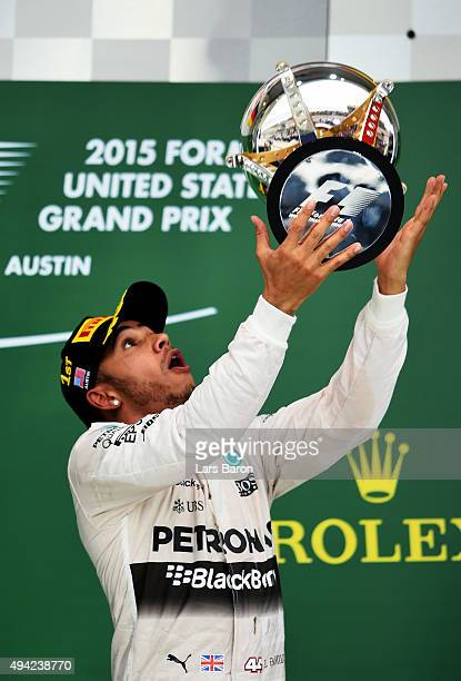 Lewis Hamilton of Great Britain and Mercedes GP throws the trophy in the air after winning the United States Formula One Grand Prix and the...