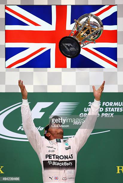 Lewis Hamilton of Great Britain and Mercedes GP throws the trophy inthe air after winning the United States Formula One Grand Prix and the...