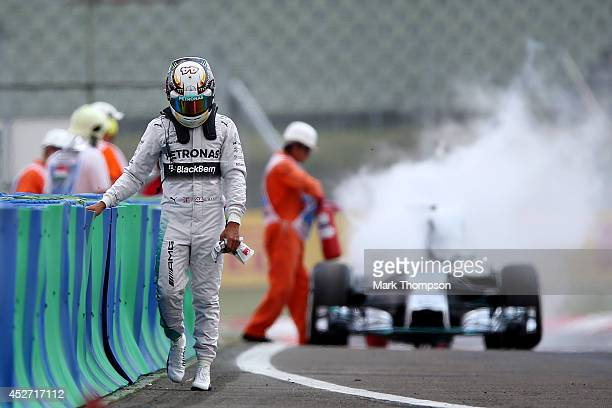 Lewis Hamilton of Great Britain and Mercedes GP walks away from his car after it caught fire during qualifying ahead of the Hungarian Formula One...