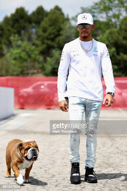 Lewis Hamilton of Great Britain and Mercedes GP walks in the Paddock with one of his dogs during previews for the Spanish Formula One Grand Prix at...