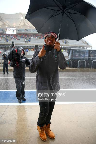 Lewis Hamilton of Great Britain and Mercedes GP walks in the pit lane with an umbrella after qualifying was suspended due to bad weather for the...