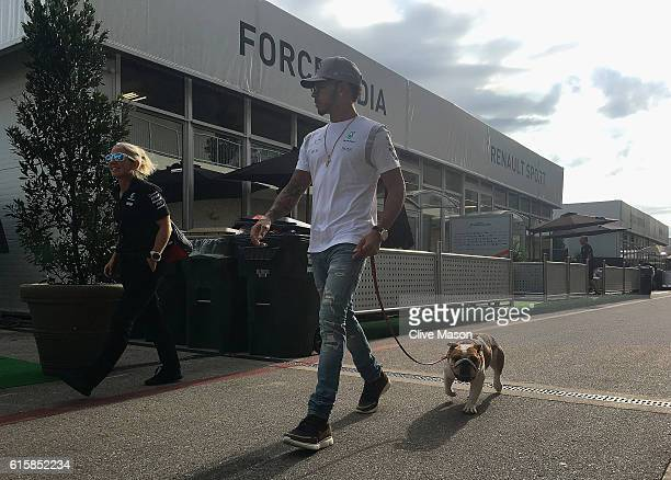 Lewis Hamilton of Great Britain and Mercedes GP walks into the paddock with his dog during previews ahead of the United States Formula One Grand Prix...