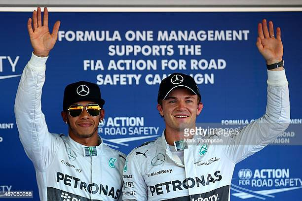 Lewis Hamilton of Great Britain and Mercedes GP waves to the crowd as he celebrates claiming pole position next to Nico Rosberg of Germany after...