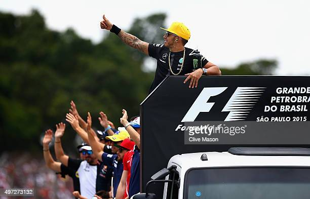 Lewis Hamilton of Great Britain and Mercedes GP waves to the crowd next to his fellow drivers during the drivers' parade before the Formula One Grand...