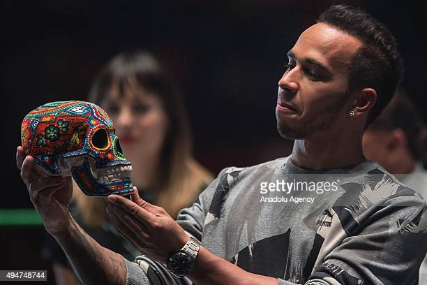 Lewis Hamilton of Great Britain and team Mercedes holds a traditional 'Calavera' during a promotional event at 'Lucha Libre' arena in Mexico City...