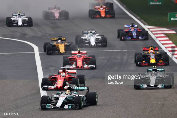 Lewis Hamilton of Great Britain driving the Mercedes AMG Petronas F1 Team Mercedes F1 WO8 leads the field into turn 1 at the start during the Formula...