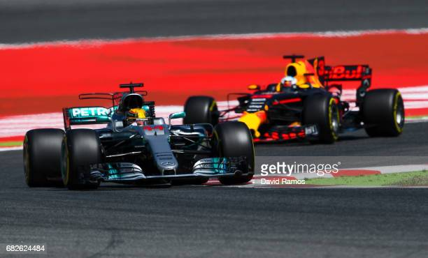 Lewis Hamilton of Great Britain driving the Mercedes AMG Petronas F1 Team Mercedes F1 WO8 and Daniel Ricciardo of Australia driving the Red Bull...