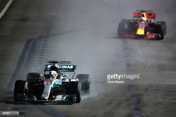 Lewis Hamilton of Great Britain driving the Mercedes AMG Petronas F1 Team Mercedes F1 WO8 leads Daniel Ricciardo of Australia driving the Red Bull...
