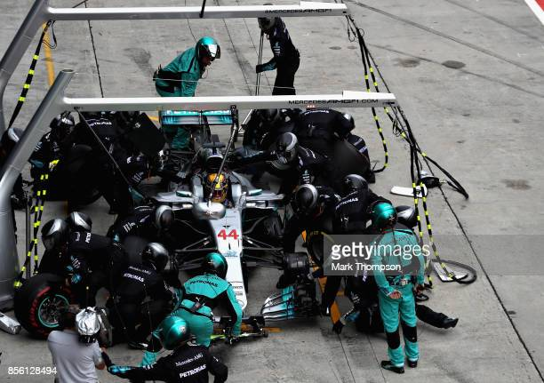 Lewis Hamilton of Great Britain driving the Mercedes AMG Petronas F1 Team Mercedes F1 WO8 makes a pit stop for new tyres during the Malaysia Formula...
