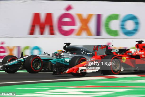 Lewis Hamilton of Great Britain driving the Mercedes AMG Petronas F1 Team Mercedes F1 WO8 passes Sebastian Vettel of Germany driving the Scuderia...