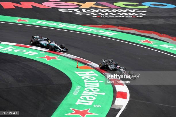 Lewis Hamilton of Great Britain driving the Mercedes AMG Petronas F1 Team Mercedes F1 WO8 follows Romain Grosjean of France driving the Haas F1 Team...