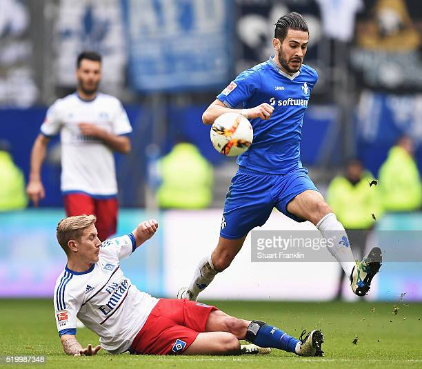 Lewis Holby of Hamburg is challenged by Jérôme Gondorf of Darmstadt during the Bundesliga match between Hamburger SV and SV Darmstadt 98 at...