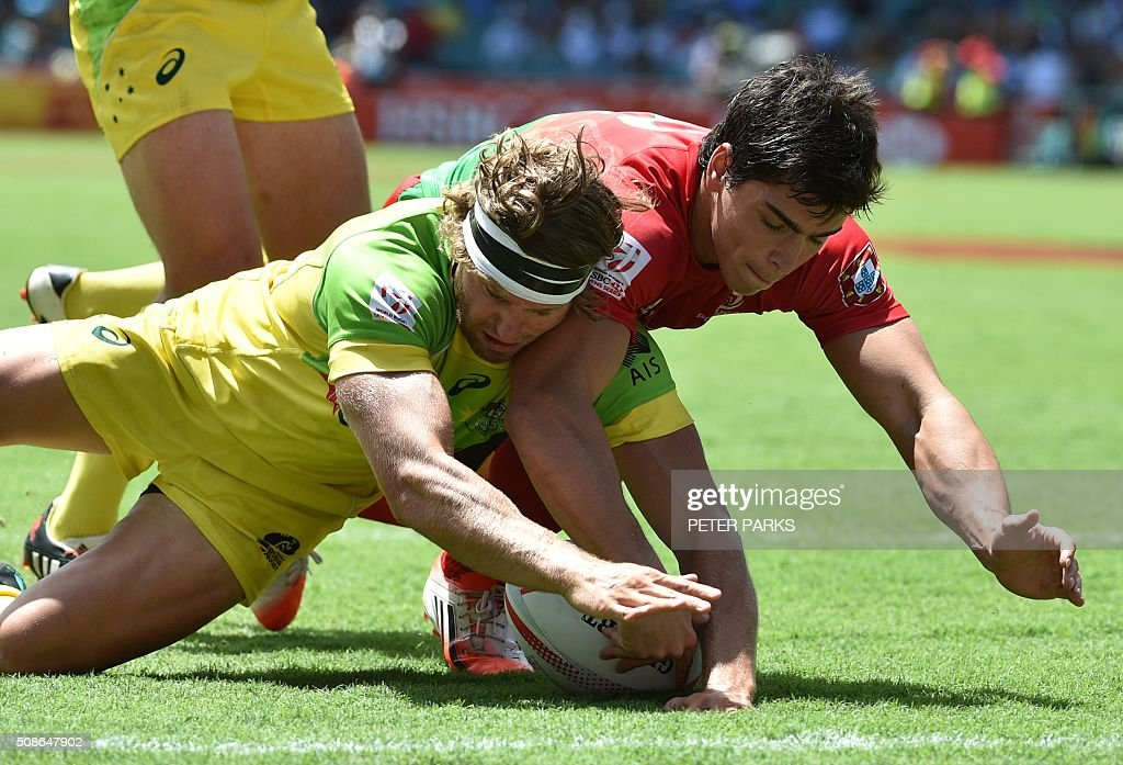 Lewis Holland (L) of Australia fights for the ball with Vasco Ribeiro (R) of Portugal in their Pool A match in the Sydney Sevens rugby Union tournament in Sydney on February 6, 2016. AFP PHOTO / Peter PARKS -- IMAGE RESTRICTED TO EDITORIAL USE - NO COMMERCIAL USE / AFP / PETER PARKS