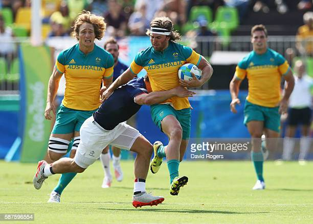 Lewis Holland of Australia is tackled by Steeve Barry of France during the Men's Rugby Sevens Pool B match between Australia and France on Day 4 of...