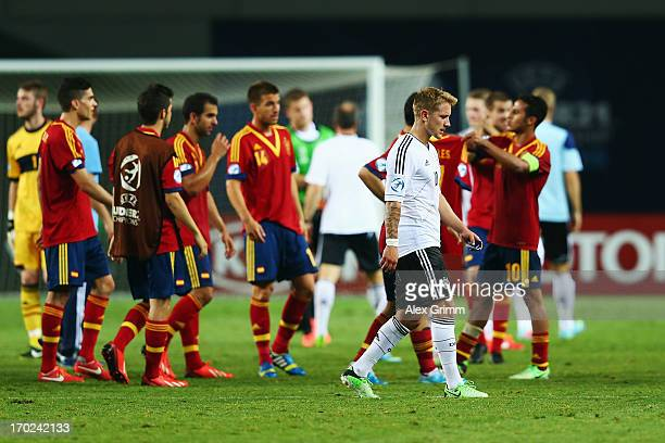 Lewis Holtby of Germany walks past the Spanish players after the UEFA European U21 Champiosnship Group B match between Germany and Spain at Netanya...