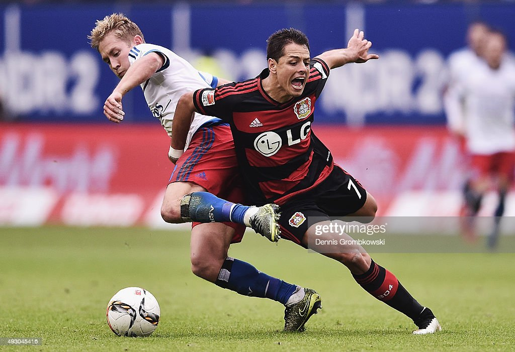 Lewis Holtby of Hamburger SV and Chicharito of Bayer Leverkusen battle for the ball during the Bundesliga match between Hamburger SV and Bayer Leverkusen at Volksparkstadion on October 17, 2015 in Hamburg, Germany.