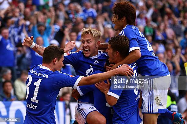 Lewis Holtby of Schalke celebrates the second goal with Julian Draxler Roman Neustaedter and Atsuto Uchida of Schalke during the Bundesliga match...