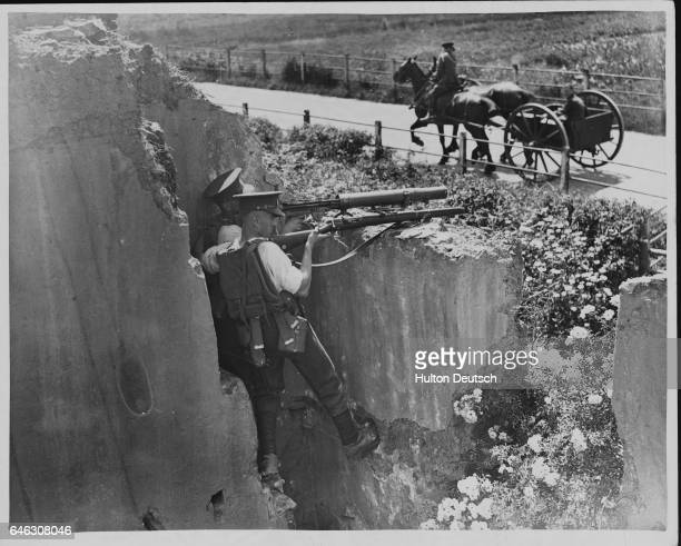 Lewis machine gunners of the 23rd London Regiment of the Territorial Army guard a road from the ruins of an old house near Corfe Castle during...