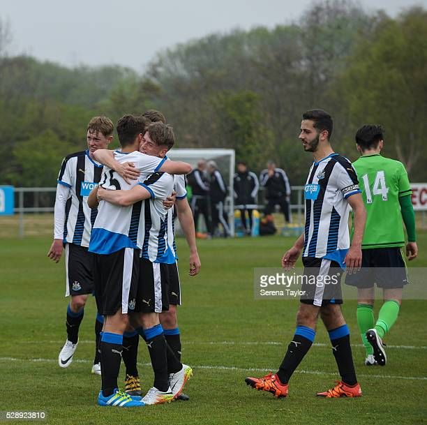 Lewis McNall of Newcastle celebrates with teammates after taking a penalty and scoring their fourth goal during the U18 Premier League Match between...