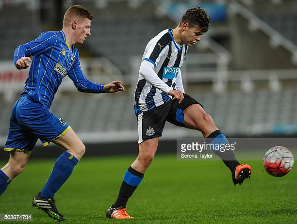 Lewis McNall of Newcastle passes the ball whilst being pursued by Seanan McKillop of Wimbledon during the U18 FA Youth Cup Match between Newcastle...