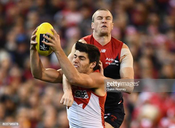 Lewis Melican of the Swans marks infront of Tom McDonald of the Demons during the round 15 AFL match between the Melbourne Demons and the Sydney...