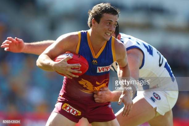 Lewis Taylor of the Lions is tackled by Todd Goldstein of the Kangaroos during the round 23 AFL match between the Brisbane Lions and the North...