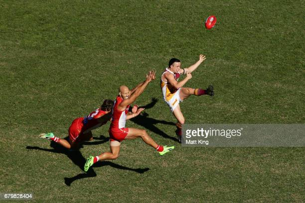 Lewis Taylor of the Lions takes a kick at goal as Jarrad McVeigh of the Swans defends during the round seven AFL match between the Sydney Swans and...