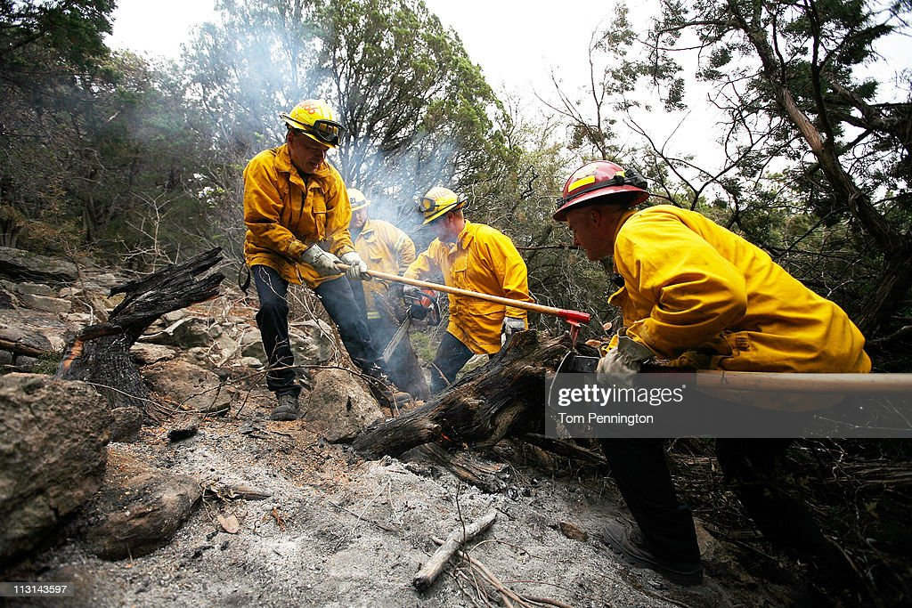 Lewisville and Coppell firefighters Tony Wright, David Green, Austin McKitrick, and Captain Mark McNeal work to extinguish a hotspot fire in rugged terrain April 24, 2011 near Graford, Texas. Cooler tempratures and high humidity has helped firefighters contain the PK Complex Fire that has destroyed more than 160 homes in the area.