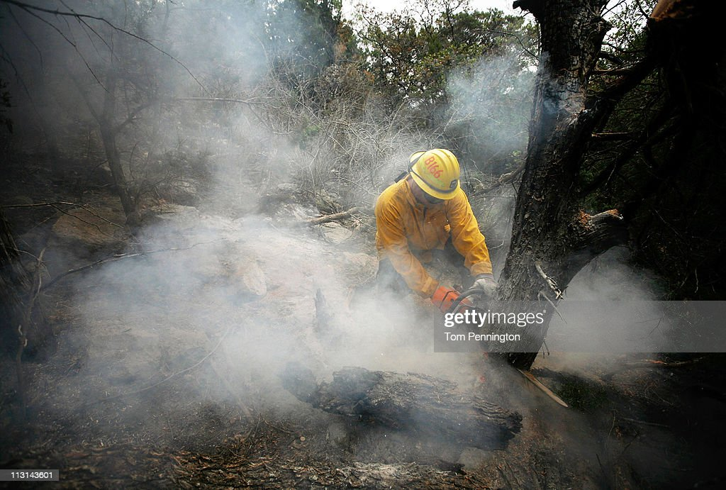 Lewisville firefighter Austin McKitrick uses a chainsaw to help extinguish a hotspot fire in rugged terrain April 24, 2011 near Graford, Texas. Cooler tempratures and high humidity has helped firefighters contain the PK Complex Fire that has destroyed more than 160 homes in the area.