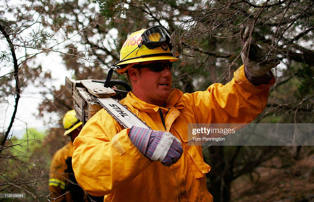 Lewisville firefighter Austin McKitrick works his way to extinguish a hotspot fire in rugged terrain April 24, 2011 near Graford, Texas. Cooler tempratures and high humidity has helped firefighters contain the PK Complex Fire that has destroyed more than 160 homes in the area.