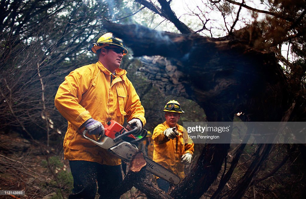 Lewisville firefighters Austin McKitrick (L) and Tony Wright use a chainsaw to help extinguish a hotspot fire in rugged terrain April 24, 2011 near Graford, Texas. Cooler tempratures and high humidity has helped firefighters contain the PK Complex Fire that has destroyed more than 160 homes in the area.