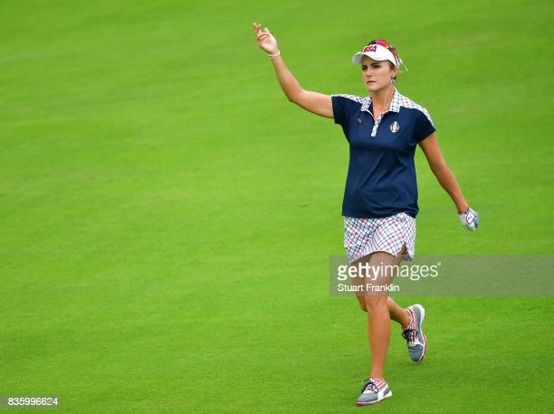 Lexi Thompson of Team USA encourages the fans during the final day singles matches of The Solheim Cup at Des Moines Golf and Country Club on August...
