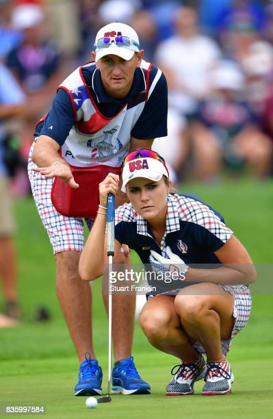 Lexi Thompson of Team USA lines up a putt with her caddie during the final day singles matches of The Solheim Cup at Des Moines Golf and Country Club...
