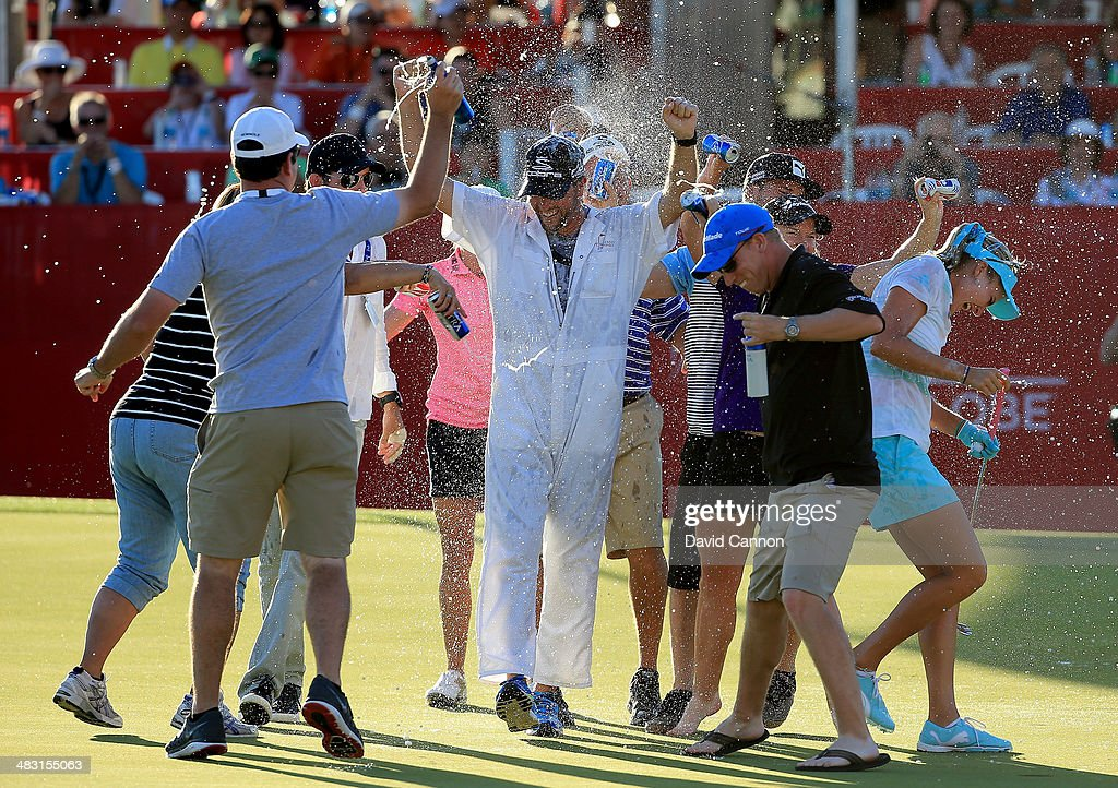 Lexi Thompson of the USA and her brother caddie Benji Thompson are soaked by family and friends on the 18th green after her three shot win during the final round of the 2014 Kraft Nabisco Championship on the Dinah Shore Tournament Course at Mission Hills Country Club on April 6, 2014 in Rancho Mirage, California.