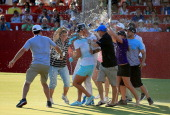 Lexi Thompson of the USA and her brother caddie Benji Thompson are soaked by family and friends on the 18th green after her three shot win during the...