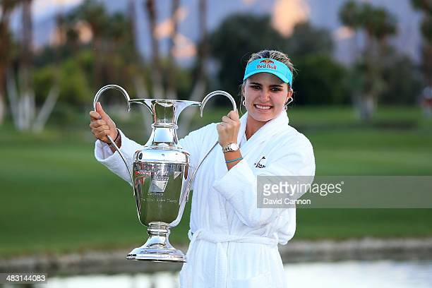 Lexi Thompson of the USA proudly holds the trophy after her three shot win during the final round of the 2014 Kraft Nabisco Championship on the Dinah...