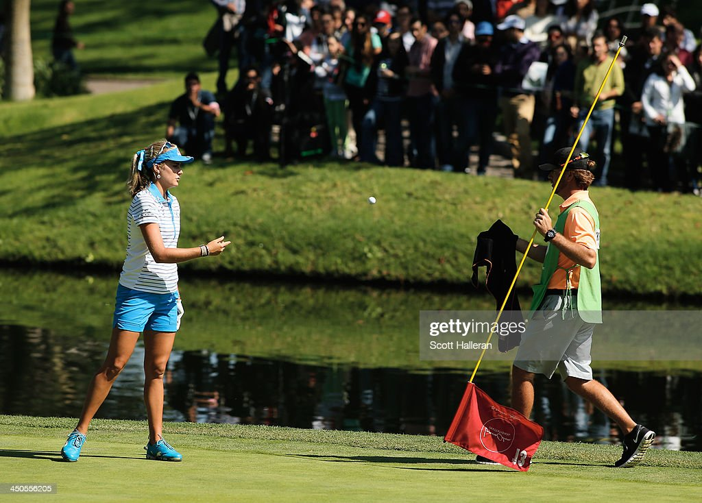 Lexi Thompson of the USA waits with her caddie Benji Thompson on the 13th green hole during the final round of the Lorena Ochoa Invitational Presented by Banamex at the Guadalajara Country Club on November 17, 2013 in Guadalajara, Mexico.