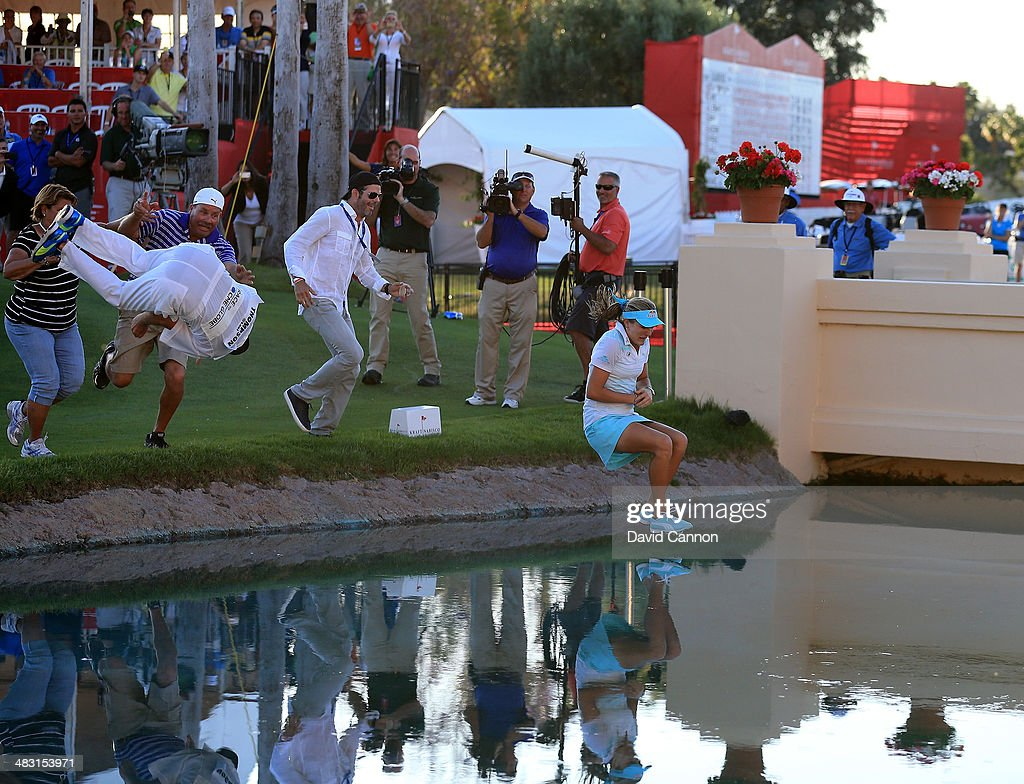 Lexi Thompson of the USA with her caddie and family in the traditional jump into Poppy's Pond after her three shot win during the final round of the 2014 Kraft Nabisco Championship on the Dinah Shore Tournament Course at Mission Hills Country Club on April 6, 2014 in Rancho Mirage, California.