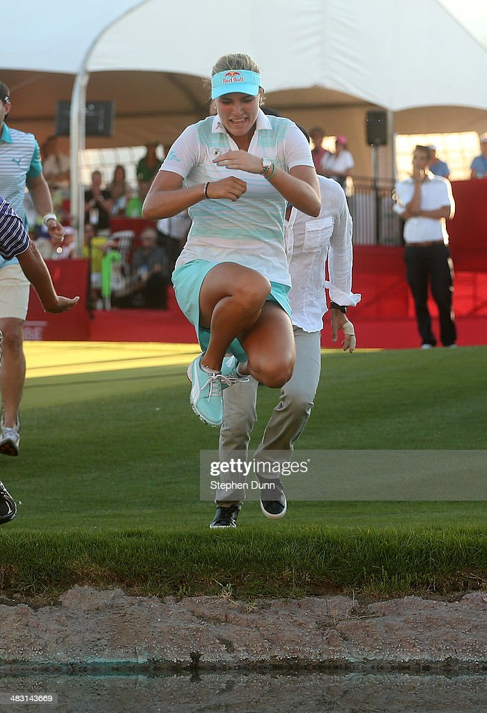 Lexi Thompson takes the leap into Poppie's Pond after her victory during the final round of the Kraft Nabisco Championship at Mission Hills Country Club on April 6, 2014 in Rancho Mirage, California.