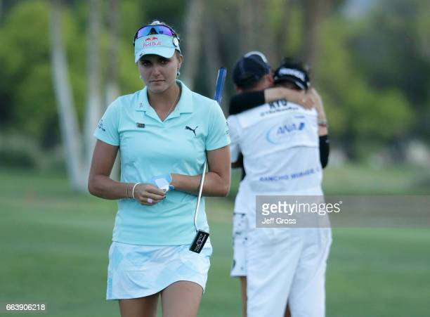 Lexi Thompson walks off the 18th green as So Yeon Ryu of the Republic of Korea celebrates with her caddie after Ryu defeated Thompson in a playoff...