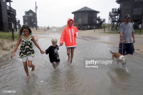 Lexus Meekins and her aunt Jessica Meekins help Lexus' brother Freeman Meekins walk along a flooded street away from the beach in Buxton North...