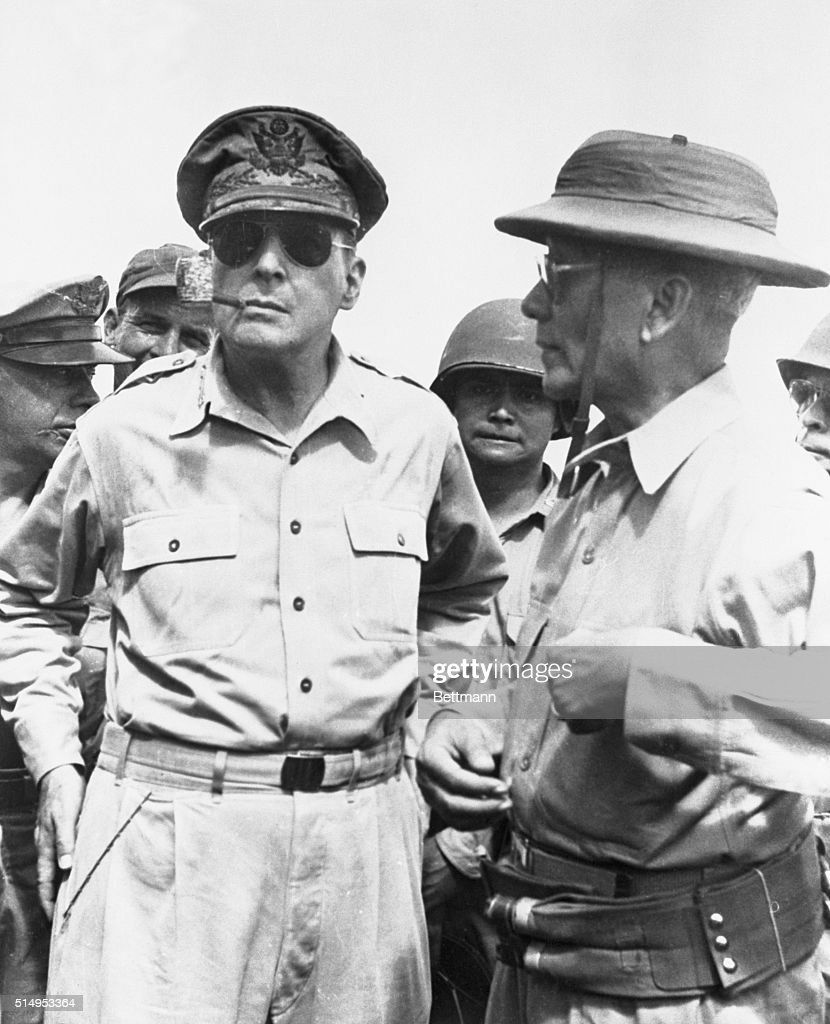 United States General Douglas MacArthur standing with soldiers in Leyte. MacArthur has his standered corn-cob pipe and aviator style sun glasses.