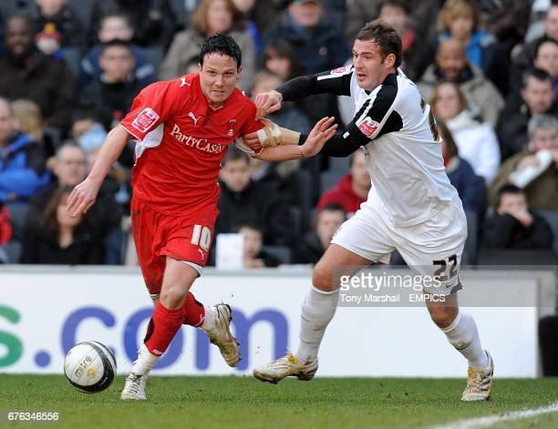 Leyton Orient's Sean Thornton and Milton Keynes Dons' Peter Leven battle for the ball
