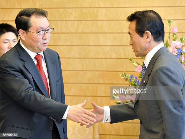 Li Changchun a standing committee member of Chinese Communist Party's Political Bureau shakes hands with Japanese Prime Minister Taro Aso prior to...