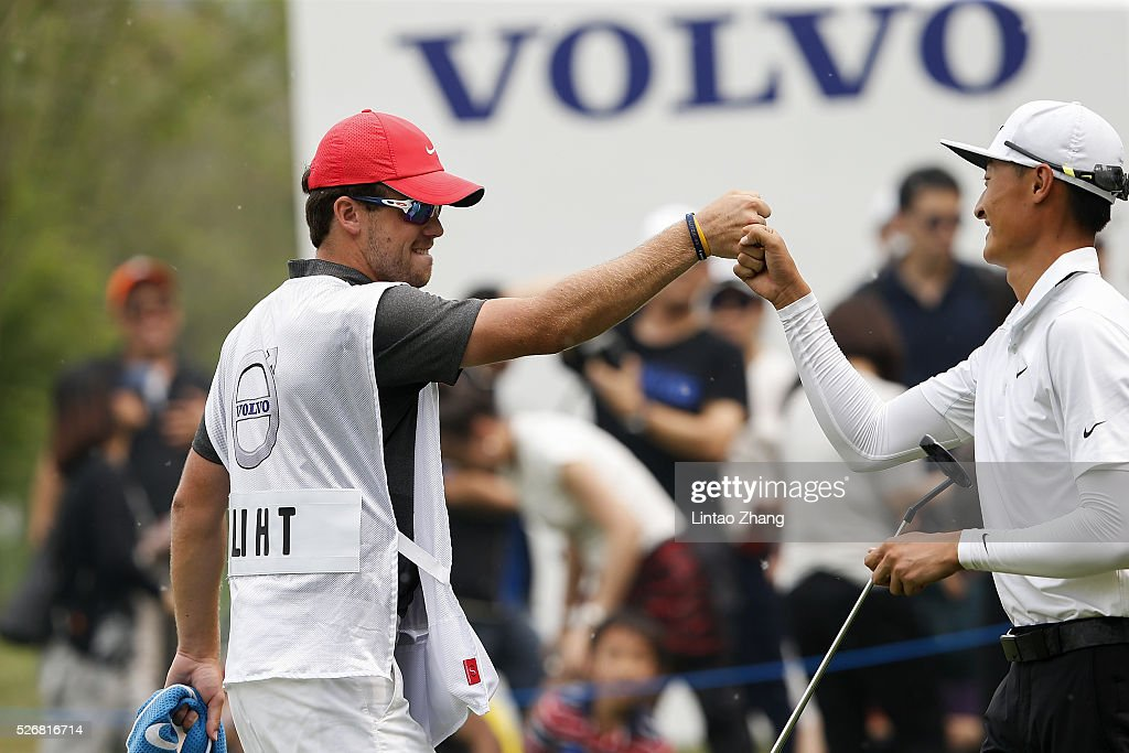 Li Haotong of China elebrates after plays a shot with his caddy during the final round of the Volvo China open at Topwin Golf and Country Club on May 1, 2016 in Beijing, China.