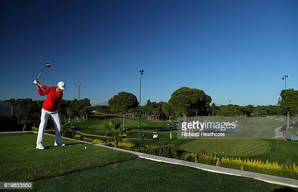 Li Haotong of China hits a shot from the 16th tee which is ontop of a villa during a practise day for the Turkish Airlines Open at the Regnum Carya...