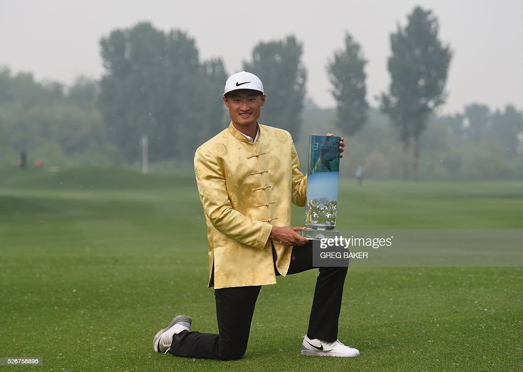 Li Haotong of China holds the trophy after winning the Volvo China Open golf tournament in Beijing on May 1, 2016. / AFP / GREG