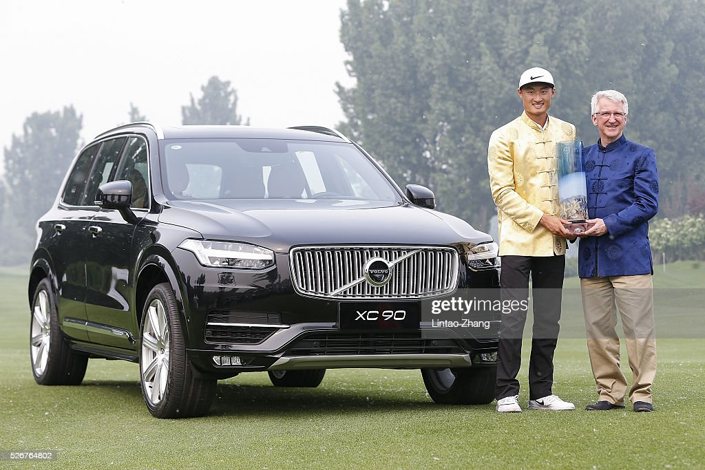 Li Haotong (L) of China holds the trophy with Senior Vice President of Volvo Cars China Operations Lars Danielson after winning the Volvo China Open at Topwin Golf and Country Club on May 1, 2016 in Beijing, China.