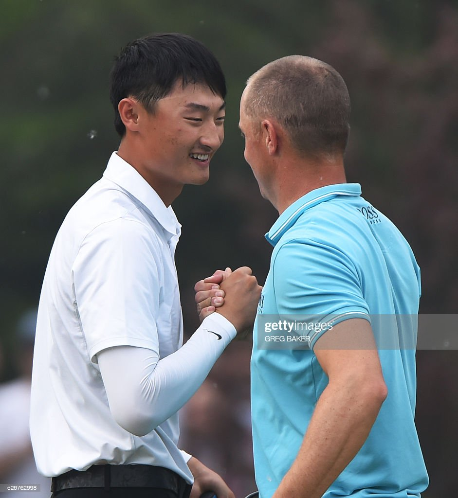 Li Haotong of China (L) is congratulated by Alex Noren of Sweden after Li won the Volvo China Open golf tournament in Beijing on May 1, 2016. / AFP / GREG