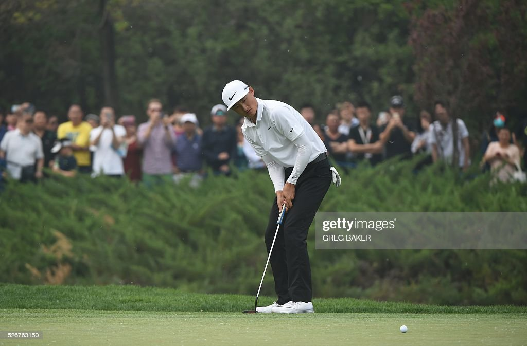 Li Haotong of China putts on the 18th green during final round of the Volvo China Open golf tournament in Beijing on May 1, 2016. / AFP / GREG